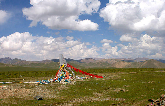 A view of the grassy Tibetan Plateau with a stone cairn decorated with prayer flags and billowing clouds above