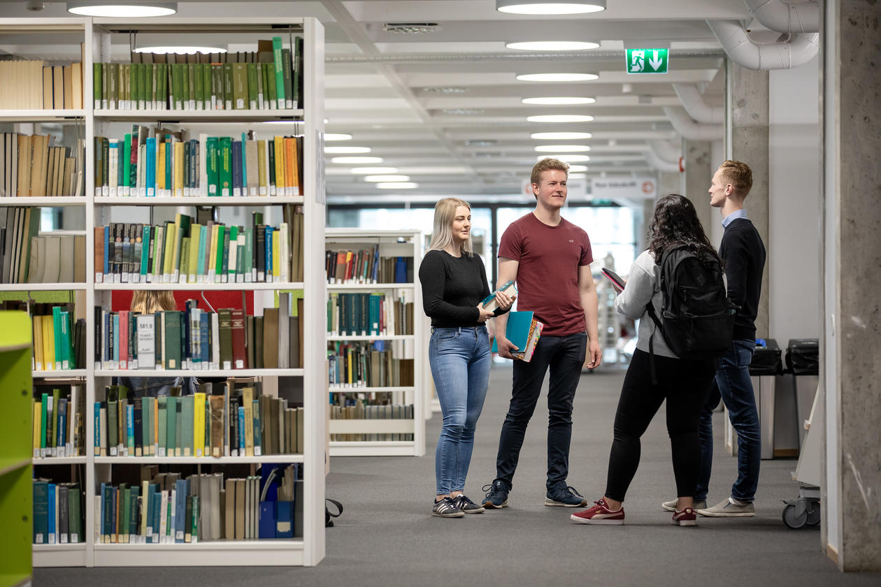 Bilde av 4 studenter som står i biblioteket og snakker sammen