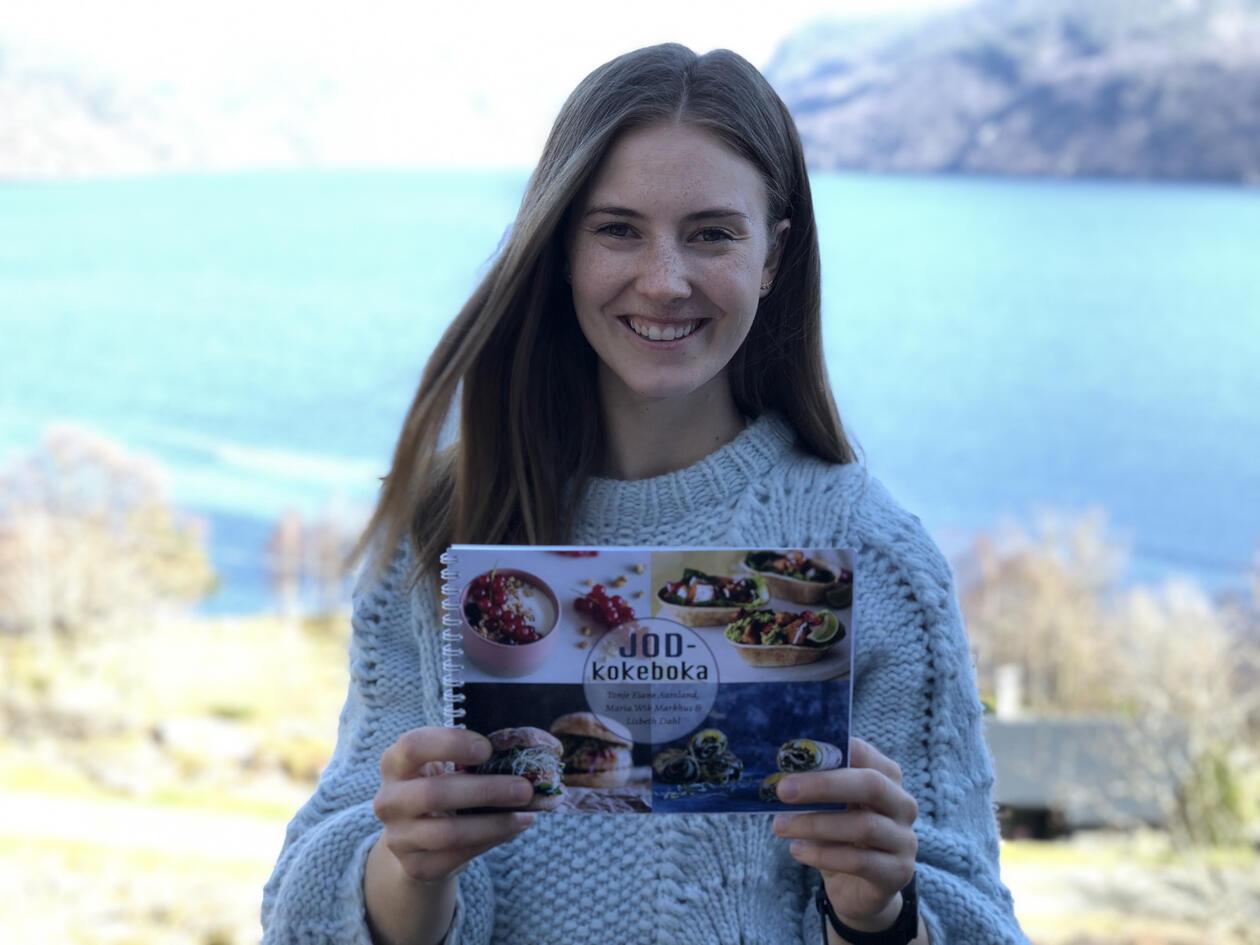 Tonje Eiane Aarsland med kokeboken sin i hånden, hun smiler. Bak henne ser man blått hav