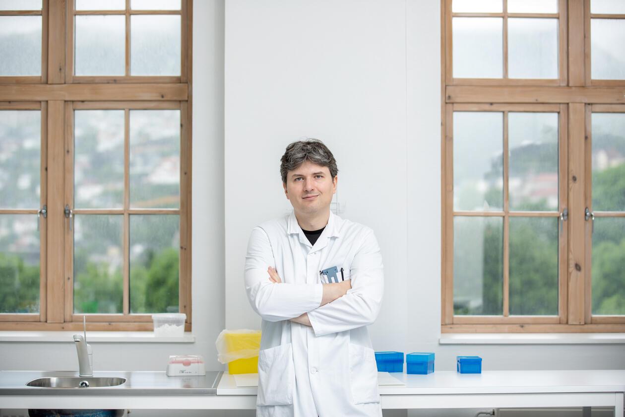 Charalamopos Tzoulis i labben. Han står med armene i kors mellom to store sprossekledde vinduer og ser rett inn i kamera. Bak ham kan man se divere utstyr til labben. Utenfor er det grønt og frodig, man kan se hus oppover skråningene.