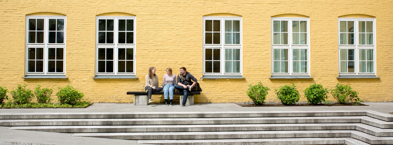 Three students sitting on a bench in front of a yellow building, Sydneshaugen skole