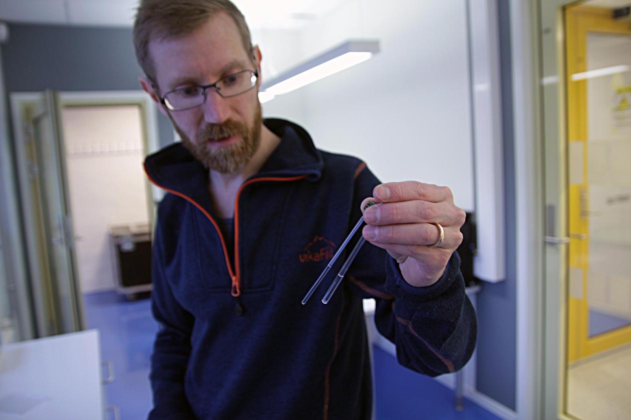 Jarl Underhaug, førsteamanuensis ved kjemisk institutt og fagansvarlig ved den norske NMR-plattformen ved UiB, viser fram kolbene som NMR-spektrometeret analyserar.