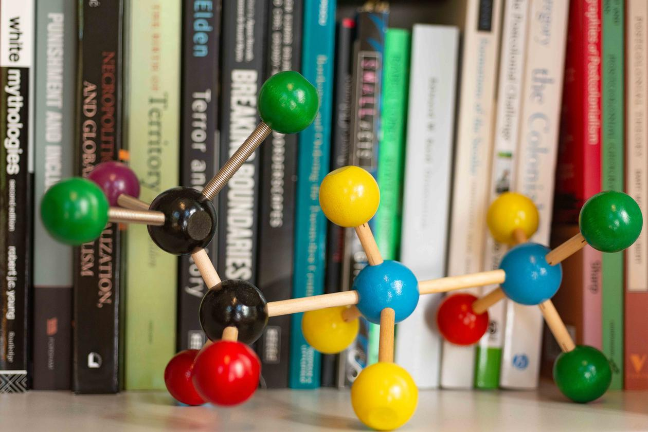 Figure of molecules in front of a row of books