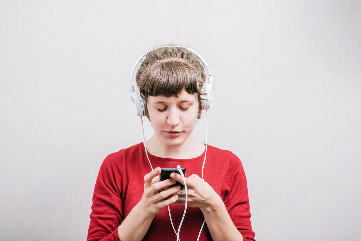 Ung jente med øreklokker ser på telefonen sin