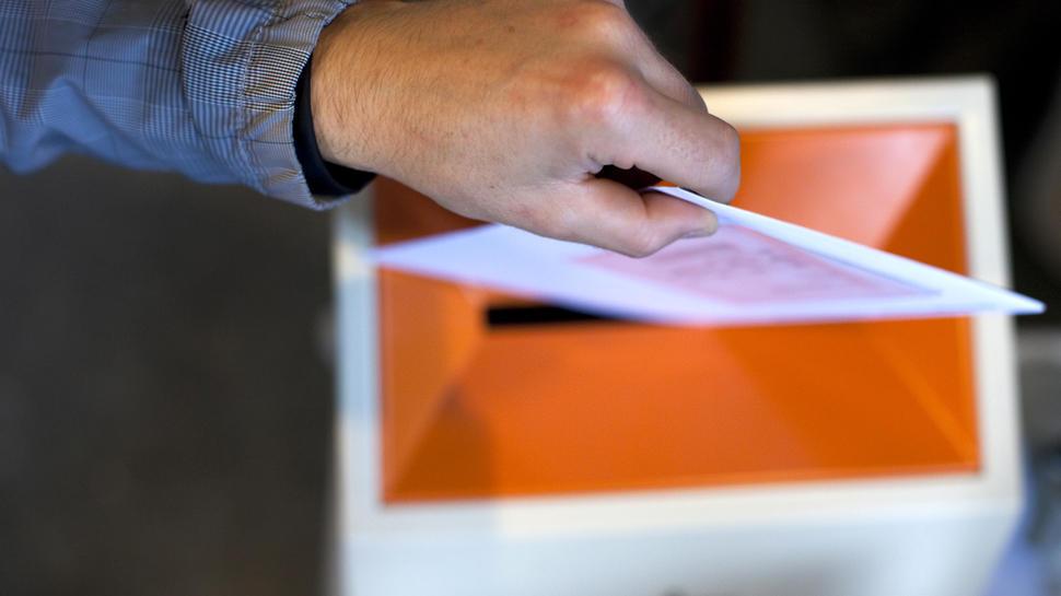 Bilde av hånd som slipper stemmeseddel i valgurne