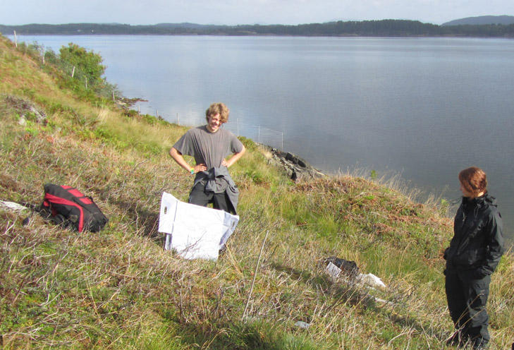 Two students surveying heathland vegetation next to a fjord