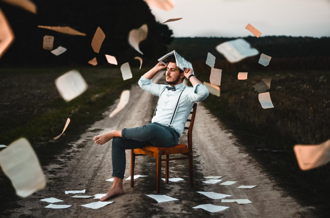 Man sitting on a chair on a road with paper flying aroud