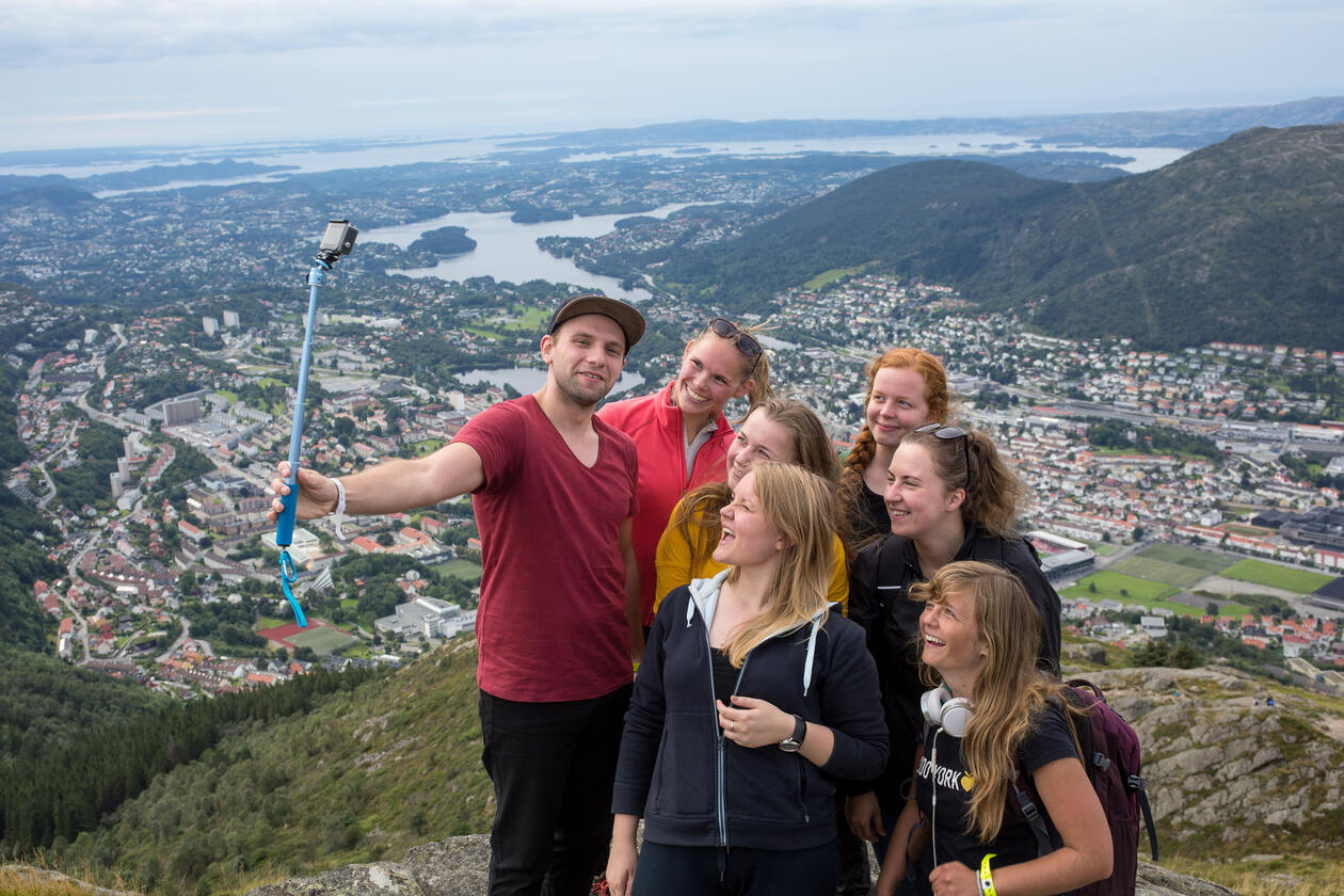 Seven exchange students are taking a selfie from the top of a mountain in bergen with a view of the city below them.