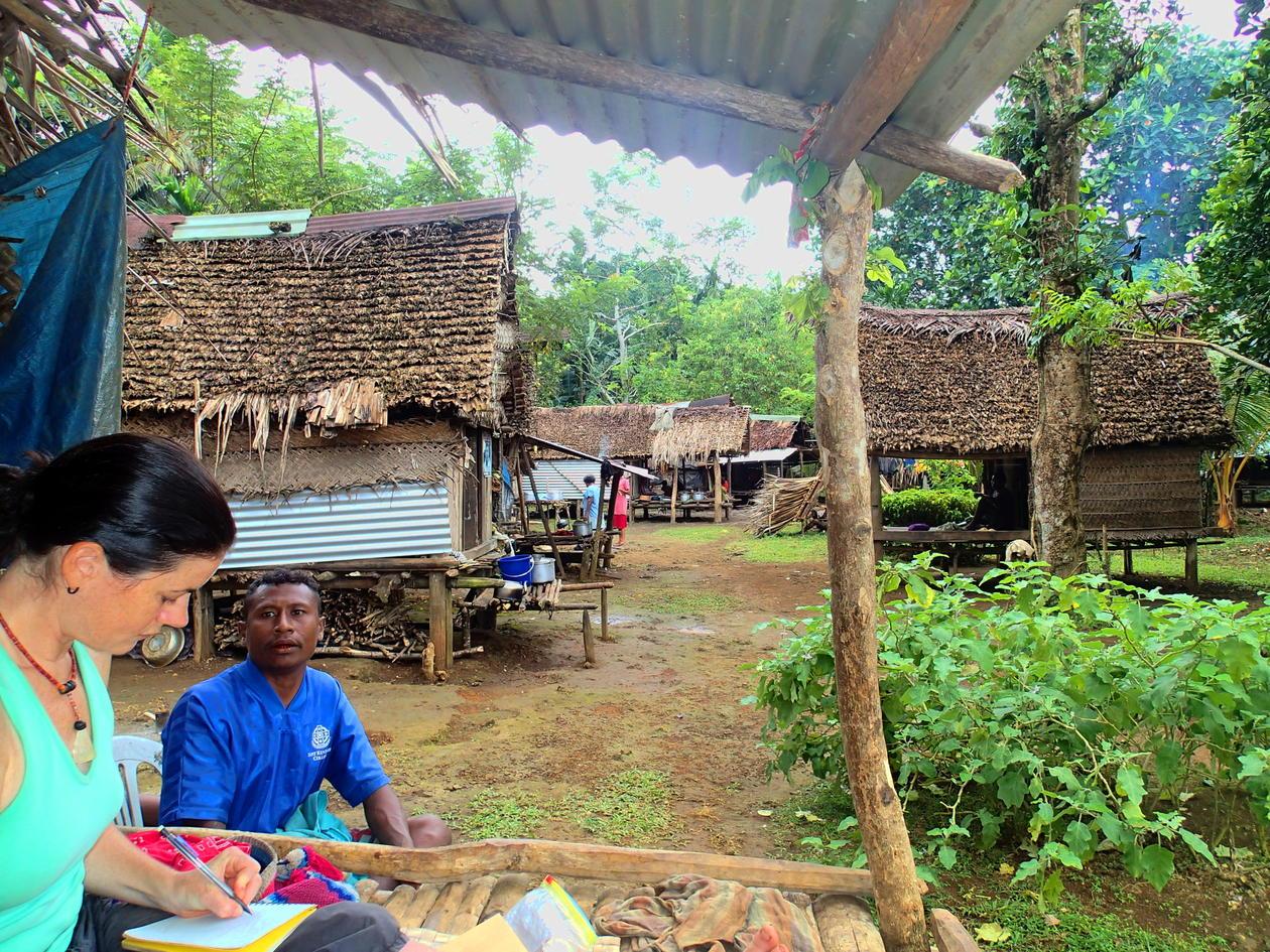 MacCarthy i felten, tar feltnotater sittende utenfor en tradisjonell Trobriander hytte