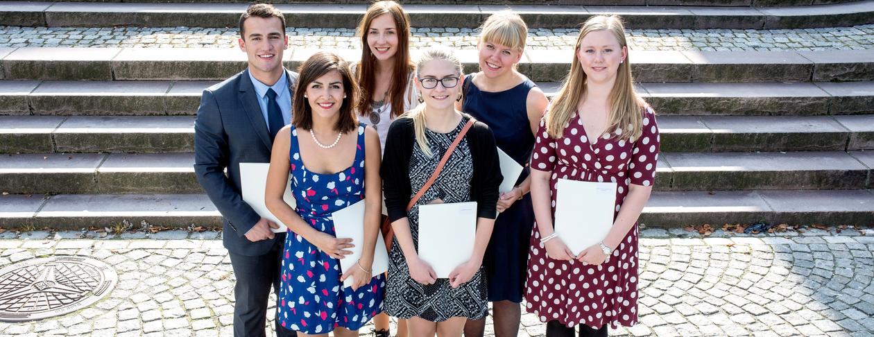 Seks studenter i solskinnet etter at de har mottatt vitnemålet sitt under Vitnemålsseremonien 2014