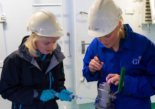 Geochemists Ingunn Thorseth and Desiree Roerdink sampling water from a sediment core
