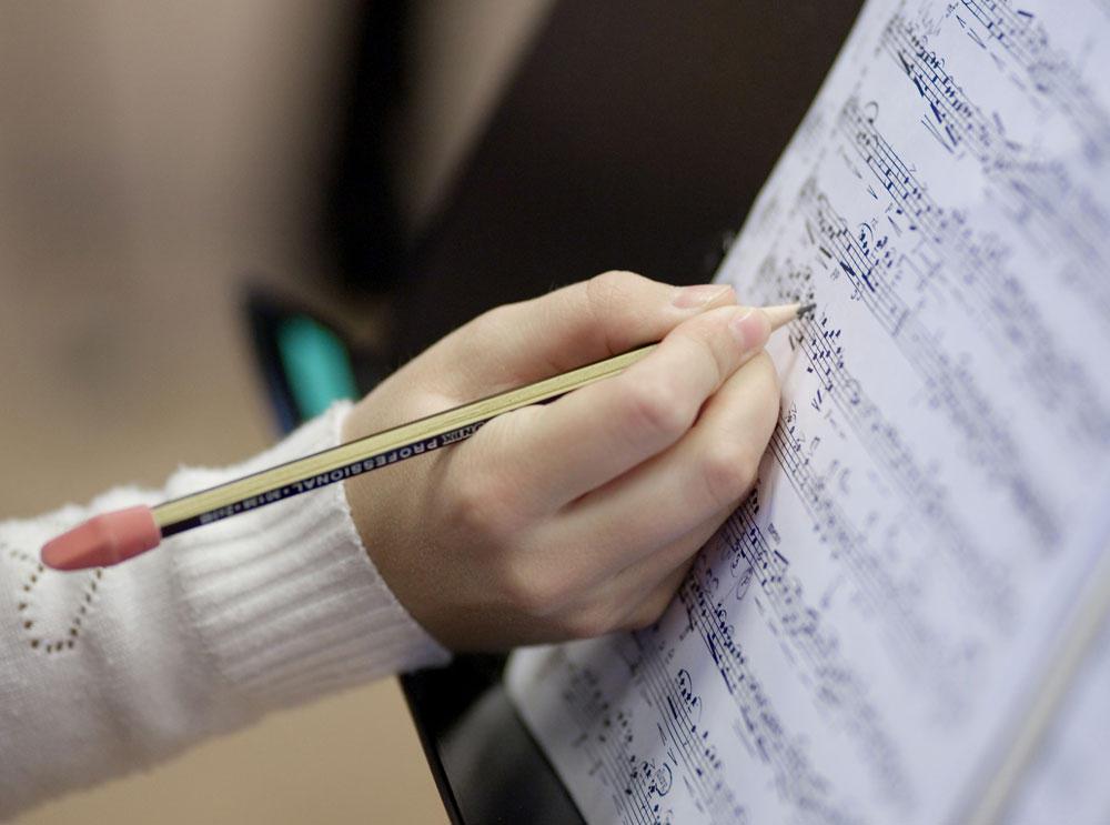 Nærbilde av hånd med blyant og noter