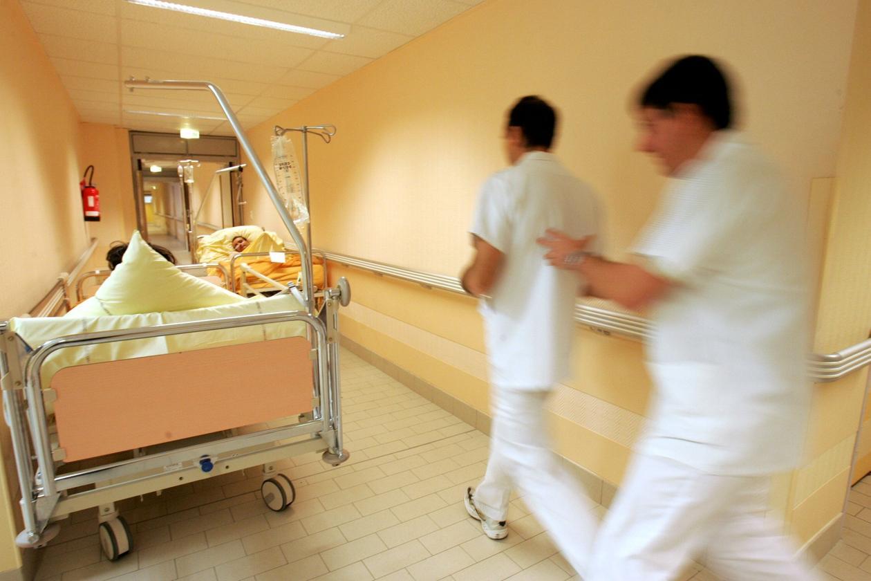 Bilde fra et sykehus hvor to ansatte haster forbi to sengeliggende korridorpasienter