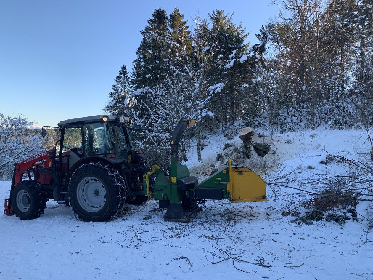 En traktor med vedkutter, tre og blå himmel i bakgrunnen, snø på bakken