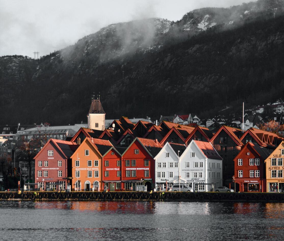 Bygninger foran vann, fjell