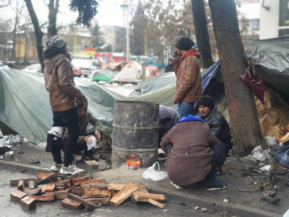 Migranter samler seg rundt et bål ved Tuzia busstasjon