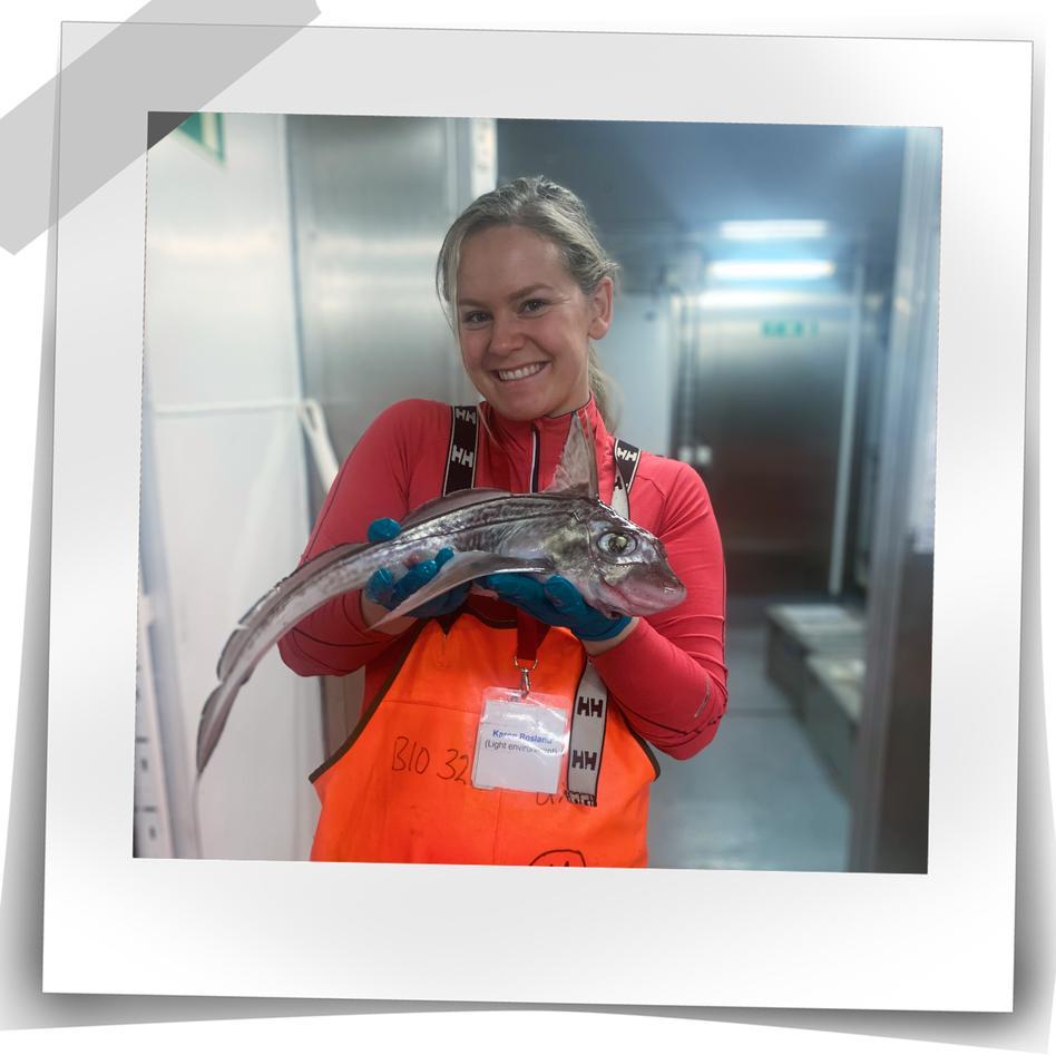 Bilde av kvinne på båt som holder en fisk mens hun smiler til kamera