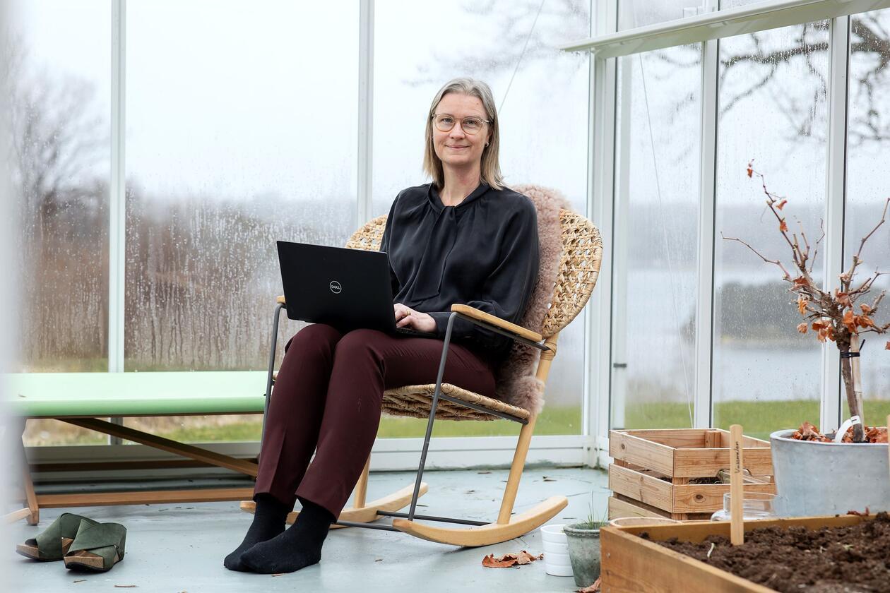 Kirsti Nordstrand sit i gyngestol med laptop og arbeider