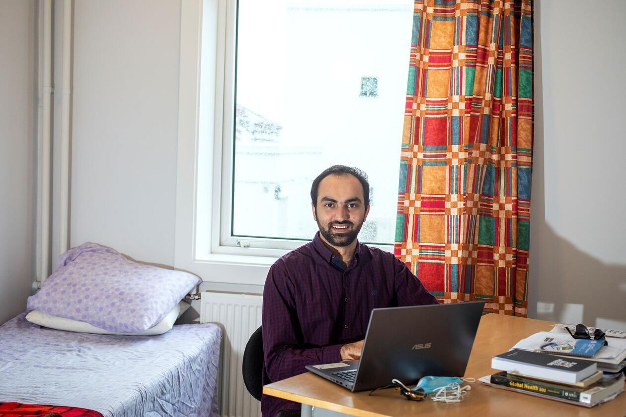 Mudasar Iqbal sit ved skrivebord på hybel og arbeidar på laptop.
