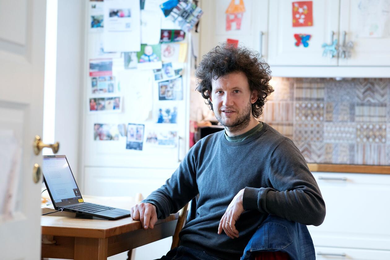 Øystein Haaland sit ved kjøkenbordet og underviser