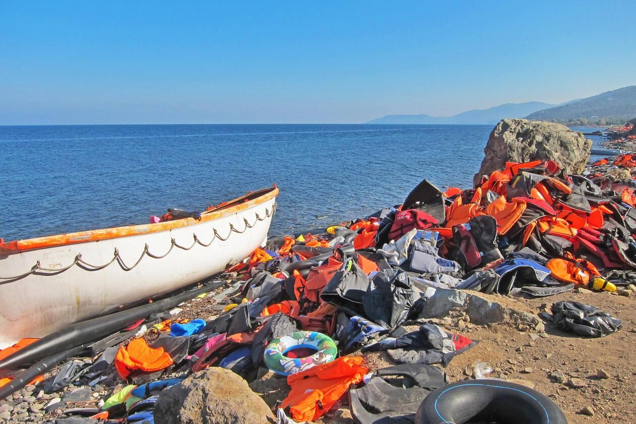 Strandet båt ved strand omgitt av redningsvester og migranters eiendeler
