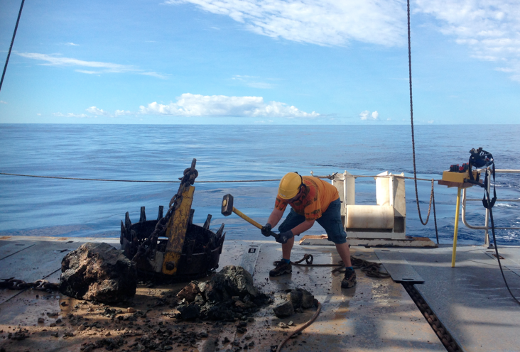 Smashing a big chunk of rock just picked up during a dredge