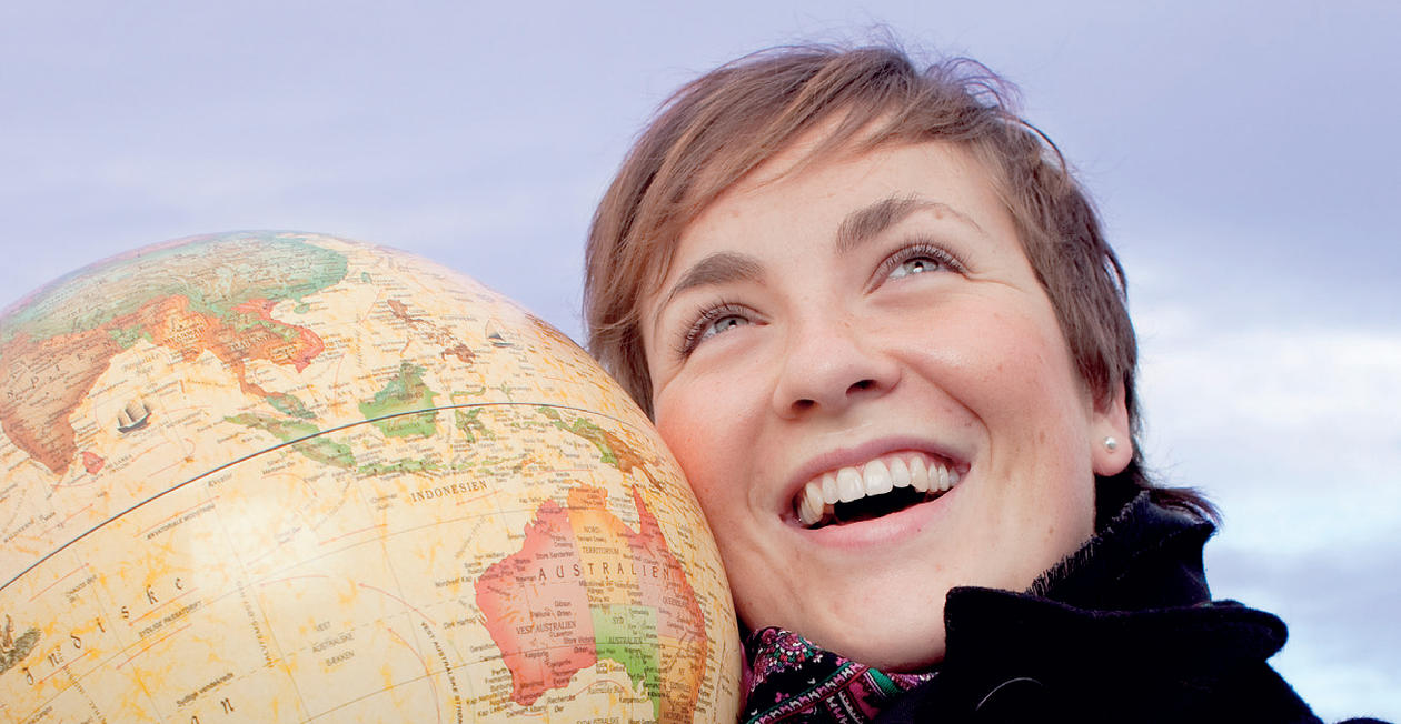 kvinne som holder globus inntil ansiktet