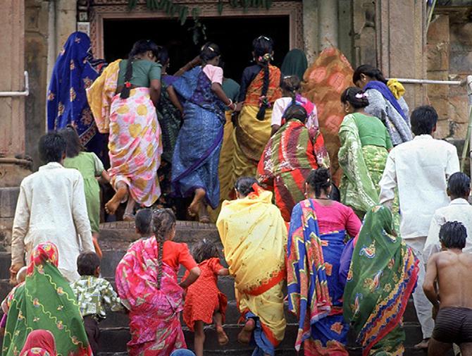 Indiske menn og kvinner i fargerike klær på vei opp en trapp til et tempel