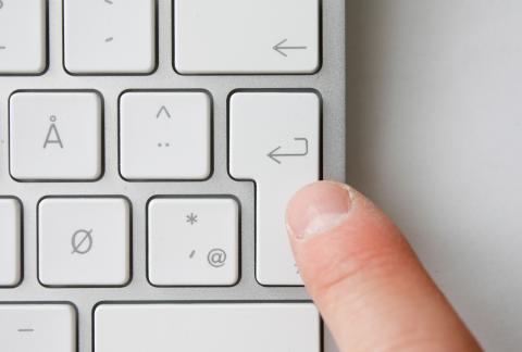 En finger som trykker på enterknappen på et tastatur