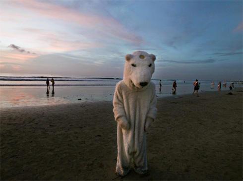 FORSTÅR IKKE : En miljøaktivist i isbjørnham demonstrerer på Kuta-stranden...
