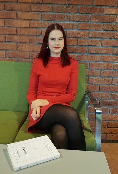 Kvinne med egen bok foran seg på et bord