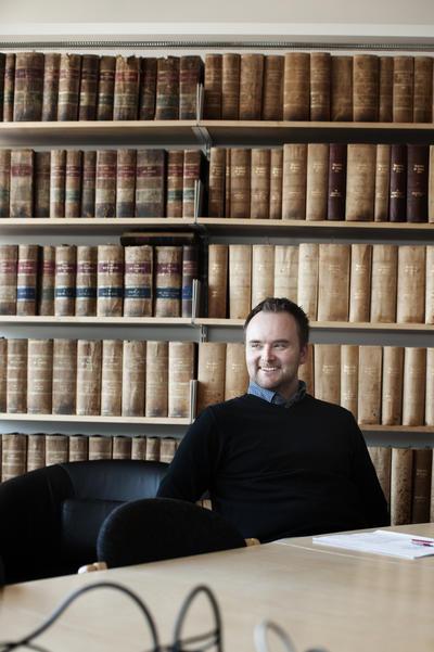 Mann sitter med bokhylle i bakgrunnen