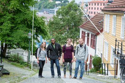 Four students standing in between the wooden houses close to Dragefjellet, the law faculty
