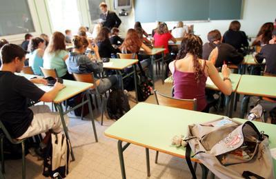 Rygger på elever i klasserom. Viser også tavle og lærer.