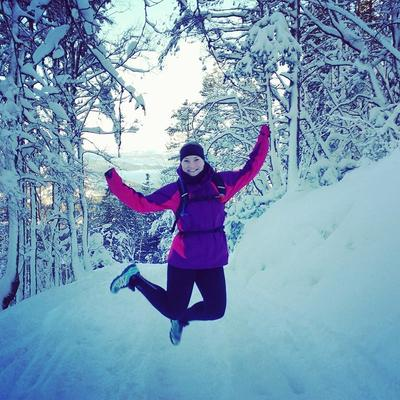 Ung kvinne som hopper i snøen