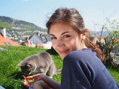 Martina is outside in the sun together with a cat.