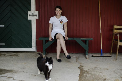 A female student sitting on a bench with a cat at her legs