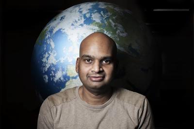 Mann står foran jordklode