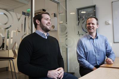 To menn som smiler og prater inne på møterom