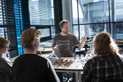 Mann sitter ved arbeidsbord, snakker med to elever