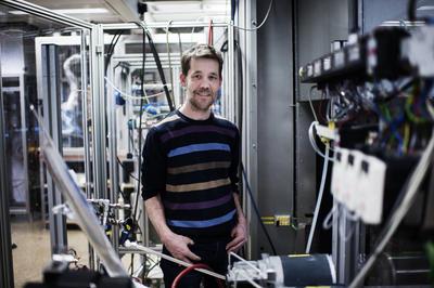 Mann står i rom med kabler og teknisk utstyr