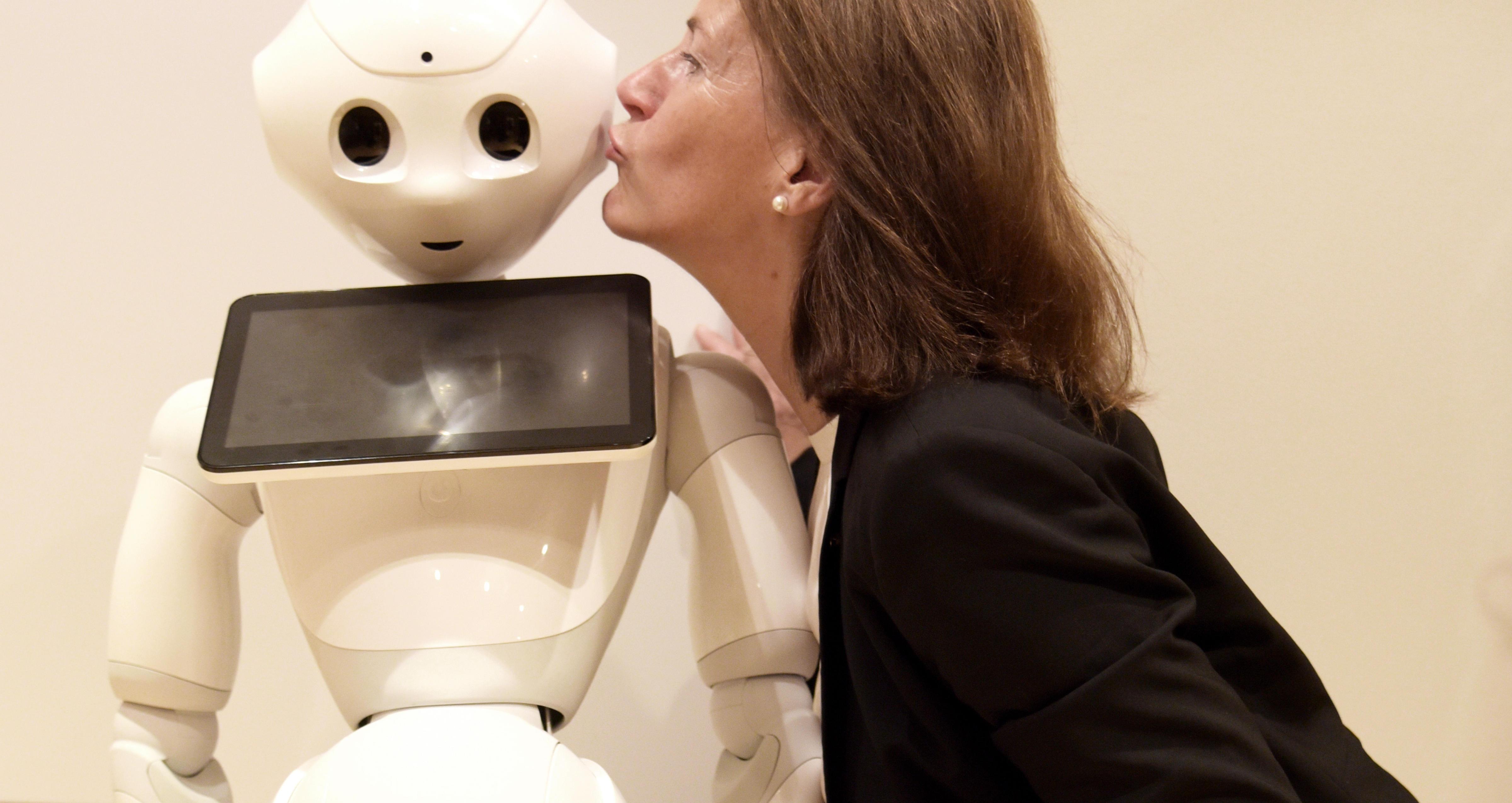 Bettina Husebø kysser roboten Pepper på kinnet.