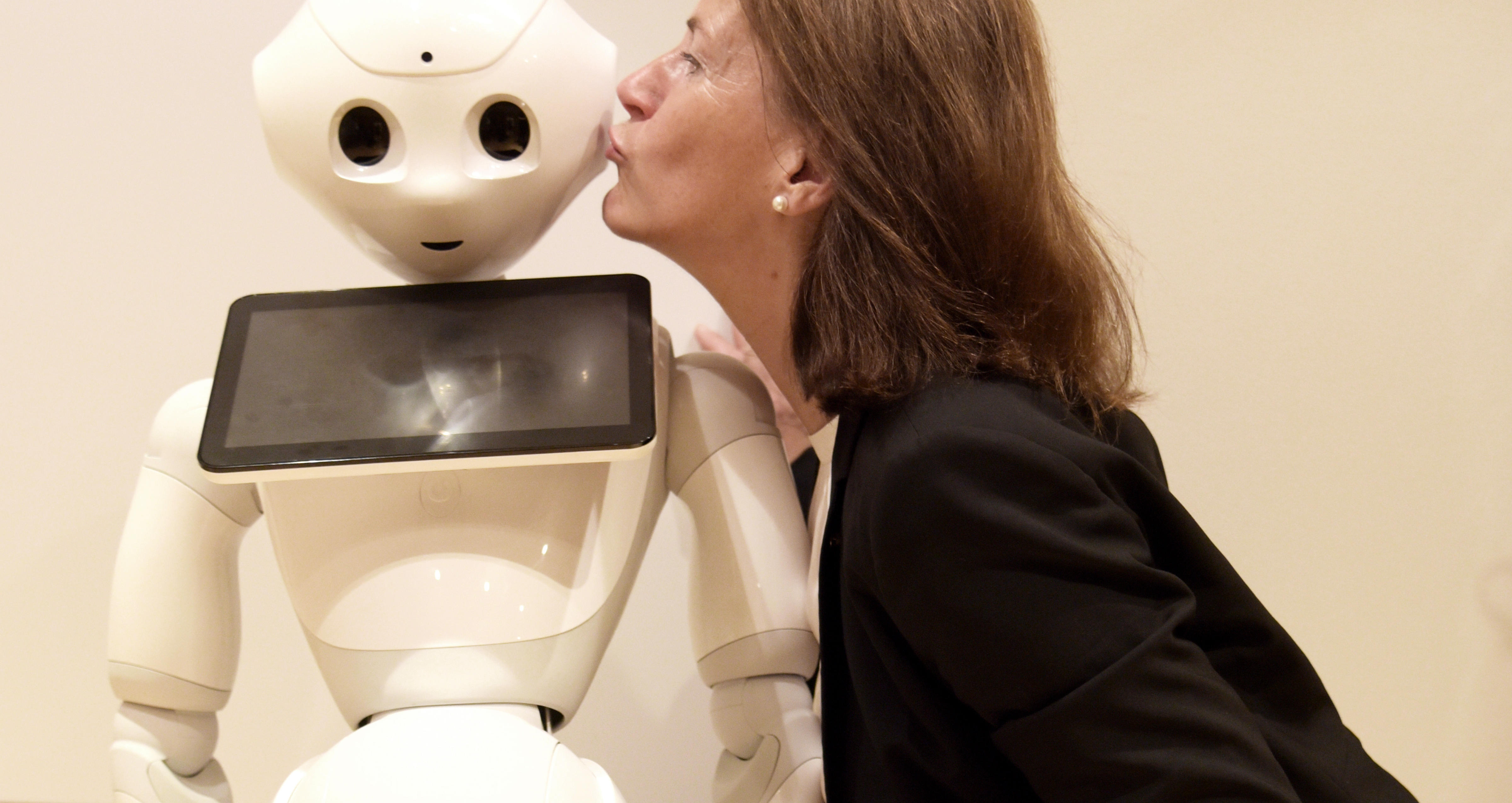 Bettina Husebø kisses the robot Pepper in Tokyo