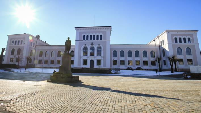 The University Museum of Bergen pictured from the front in bright sunshine in wintertime, with scattered spots of snow in front of the museum.