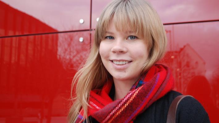 Jente med langt lyst hår står foran rød vegg