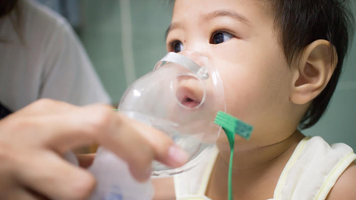 Baby with nebulizer, used to illustrate article on future public health challenges and in particular the increase in asthma and allergies.