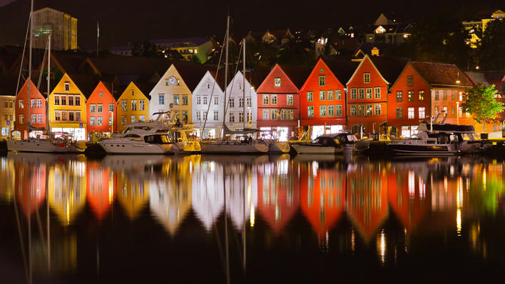 By night, Bryggen with lights on is reflected in the sea.