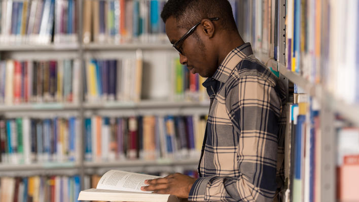 African man in library seen in profile reading a book