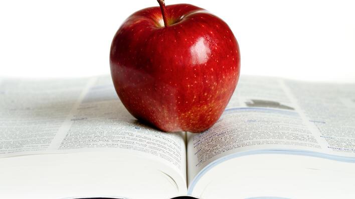 Rødt eple på oppslått bok