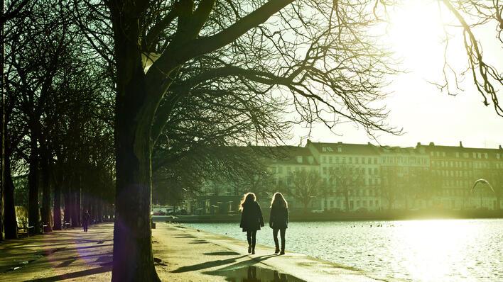 To jenter som går langs et vann, mot en bygning i høstsol.